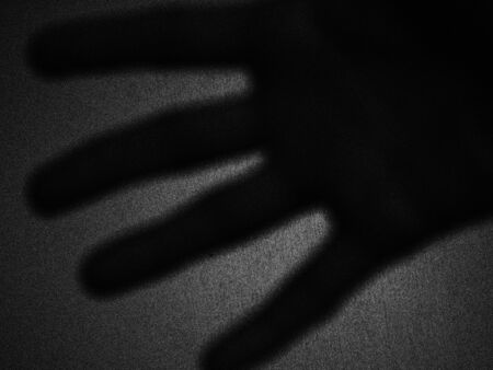Artistic shadow of a hand in backlight against a wall - Black and white picture - France.