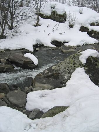 Wild small river in the mountains with snow on the banks - Les menuires station - France - The Alps. photo