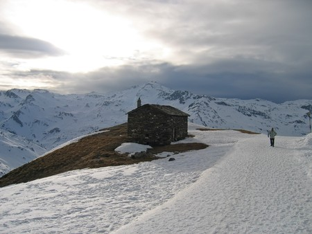 French chalet with a road full of snow and a man walikng in the background - Les menuires station - France - The Alps. Stock Photo