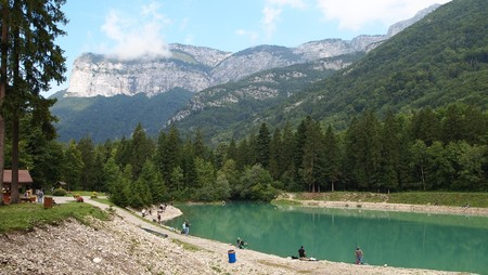 Green lake with people around and mountains with forests in the background - France - The Alps. Stock Photo