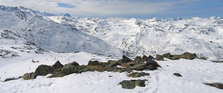 Large panoramic view of the french mountains with a skiing track bellow in the valley - Val Thorens station - France - The Alps.