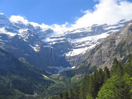 The Gavarnie Circus mountains with forest in the foreground and many rivers in the background - The Pyrenees - France.