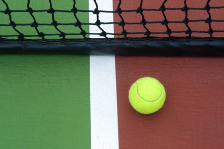 tennis  ball on line green court Stock Photo
