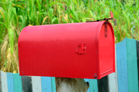 Red mail box on wooden wall photo
