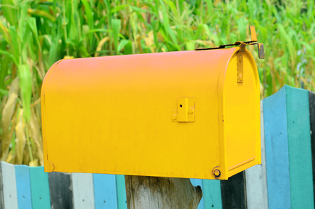 retrieve: old yellow mail box in garden Stock Photo