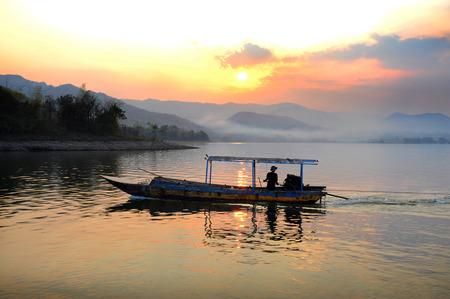 sunrise on lake with fishing boat