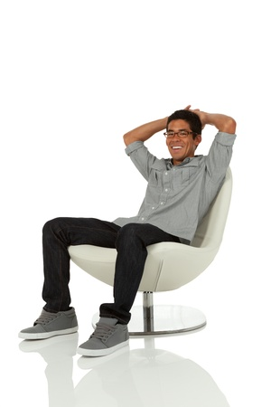comfortable chair: Man relaxed sitting on a chair looking at camera