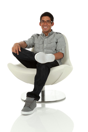 College age man sitting on a modern chair relaxed isolated on white  photo