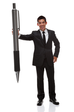 oversized: Business man holding a big pen to the side handing it forward Stock Photo