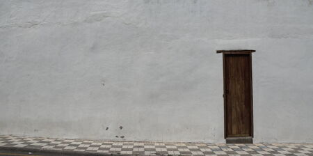 Historic wooden door in white stone wall photo