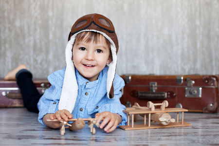 Little boy, playing with wooden planes, indoor, sitting on a suitcase  photo