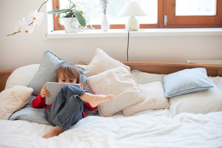 Adorable cute baby boy, playing on tablet in bed photo