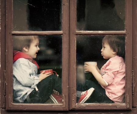 UOMO pioggia: Due ragazzi sulla finestra, ridere e bere il t�, divertirsi