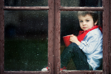 Boy on the window, smiling and drinking tea, having fun