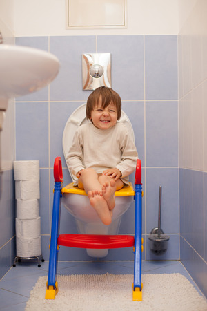 Little boy, sitting on the toiled, laughing photo