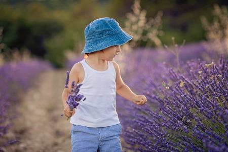Little fashionable boy having fun in lavender field  photo