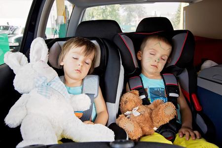 sono: Dois meninos em assentos de carro, viajar, dormir no carro com ursos de pel Imagens