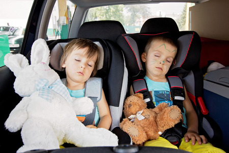 inside of: Two boys in car seats, travelling, sleeping in the car with teddy bears