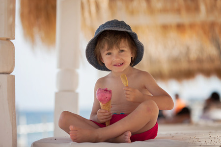 Cute shirtless boy, eating red ice cream on the beach photo