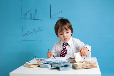Young boy, counting money and taking notes photo