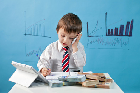 financial official: Young boy, talking on the phone, taking notes, money and tablet on the table