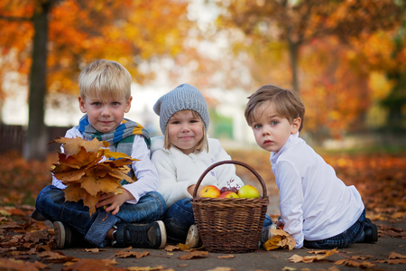 Three cute kids in the park, playing photo