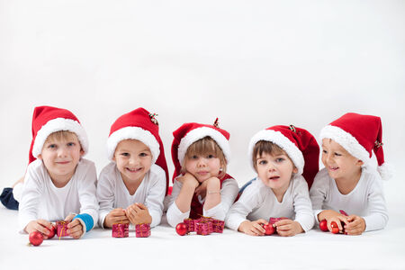 Adorable kids with santas hat, smiling at the camera, isolated on white background photo