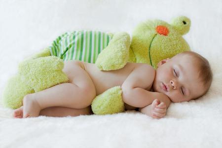bebekler: Kurbağa oyuncak ile uyuyan küçük erkek bebek,
