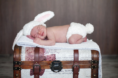 Adorable baby boy, sleeping on a trunk, dressed like bunny photo