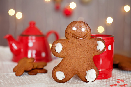 Smiling gingerbread man standing in front of a mug. Teapot and more cookies on the background. Lights and christmas decoration in the background. Red and brown colors photo