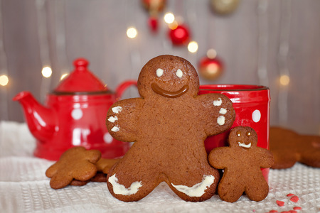 christmas cake: Smiling gingerbread man and a smaller one next to him standing in front of a mug. Teapot and more cookies on the background. Lights and christmas decoration in the background. Red and brown colors