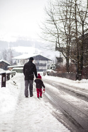 Father and son, walking in the snowy day in a village photo