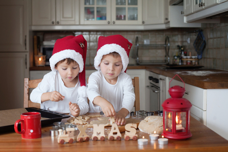 Two cute boys with santa hat, preparing cookies in the kitchen at home photo