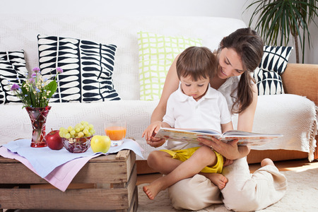 beautiful mother: Mother and child, reading a book and eating fruits