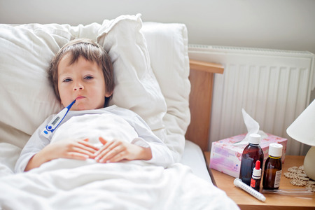 caucasian fever: Sick child boy lying in bed with a fever, resting