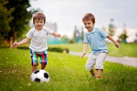 pantalones cortos: Dos niños pequeños lindos, jugar al fútbol