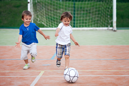 Two little boy, playing football photo