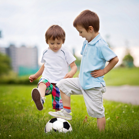 Two cute little boys, playing football photo