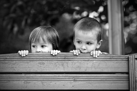 close uo: Two curious boys, looking over a wooden wall