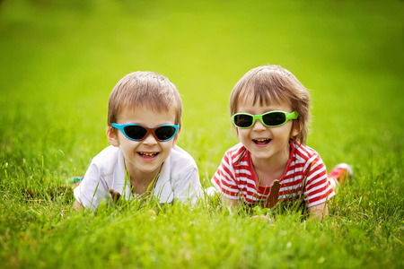peers: Cute kids with sunglasses, eating chocolate lollipops at the park Stock Photo