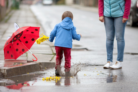 Little boy with umbrella, jumping in muddy puddles Stock Photo