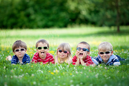 peers: Five adorable kids, lying on the grass, smiling, having fun, wearing glasses