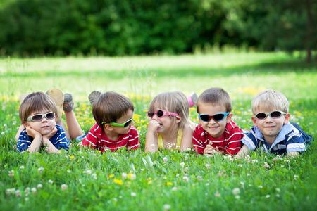 5 かわいい子供たちは、草の上に横たわる笑みを浮かべて、楽しんで、眼鏡をかけています。