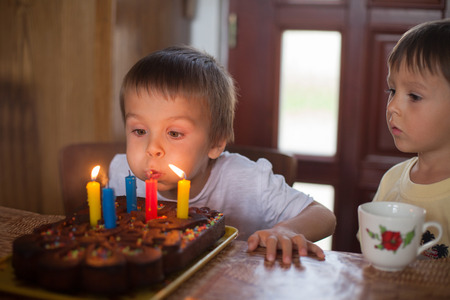 velitas de cumpleaños: Cinco años adorable niño de la celebración de su cumpleaños y soplando