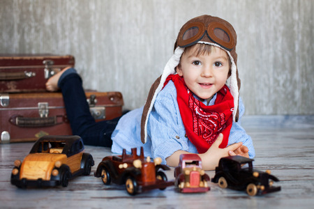 Little boy, playing with wooden cars, indoor, suitcases behind him  photo