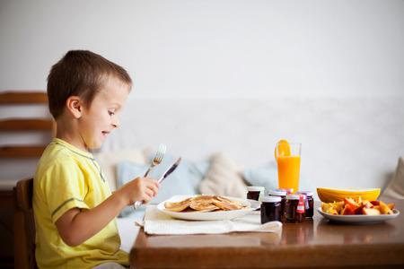 Cute boy, eating pancakes at home photo