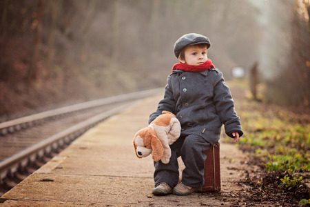 Portrait of a little boy with s suitcase and a teddy dog, waiting on a railway station Stock fotó
