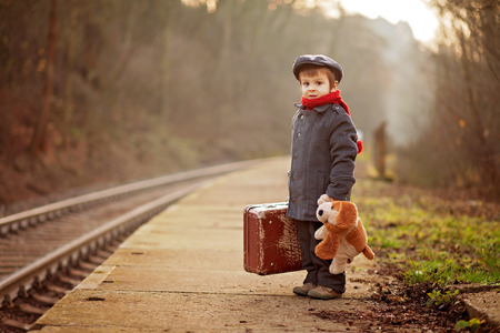 Portrait of a little boy with s suitcase and a teddy dog, waiting on a railway station Stock Photo