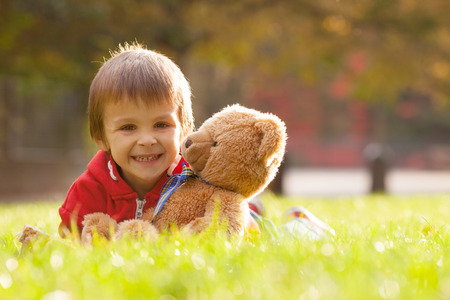 cute teddy bear: Adorable little boy with teddy bear in the park on an autumn day in the afternoon, sitting on the grass Stock Photo