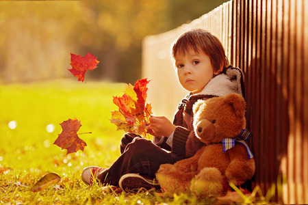 Adorable little boy with teddy bear in the park on an autumn day in the afternoon, sitting on the grass photo